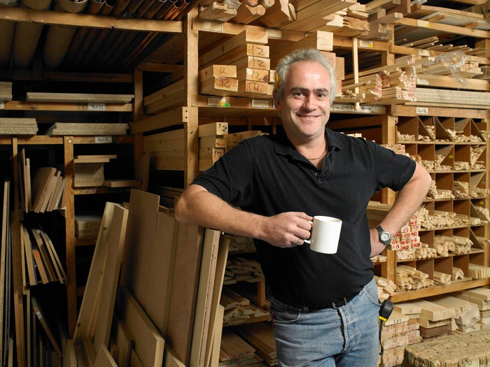 Self-employed baby boomer holding a coffee mug and smiling.