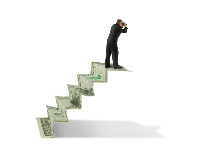 Man with binoculars on a staircase made of money, looking for something out in the distance.