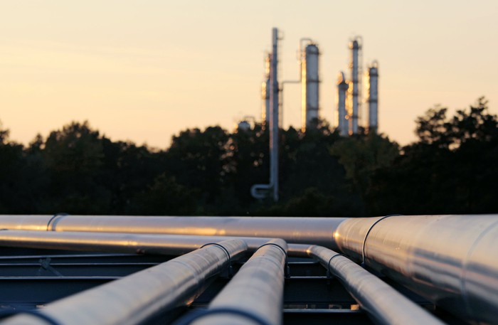 Pipelines to a refinery at dusk.