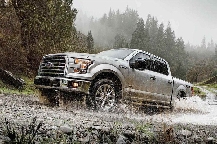 A silver 2017 Ford F-150 pickup truck driving on a wet, unpaved road