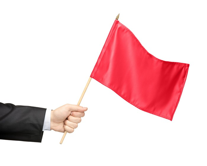 Hand holding a red flag.