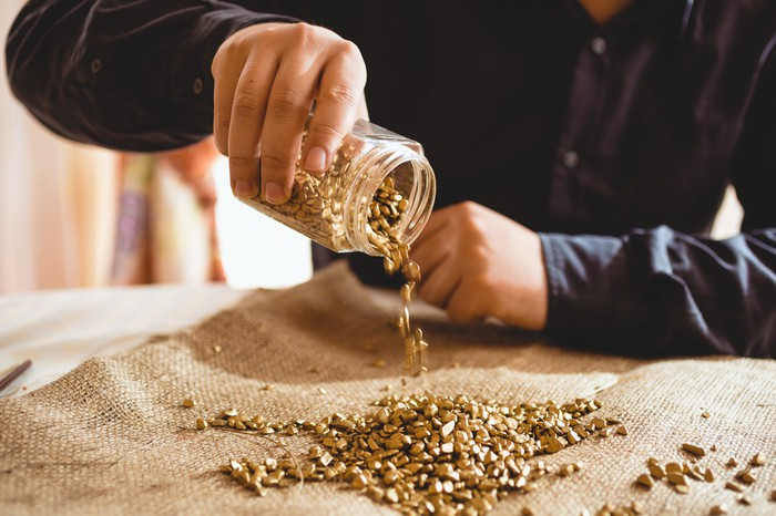 Pouring out a container of gold nuggets into a pile