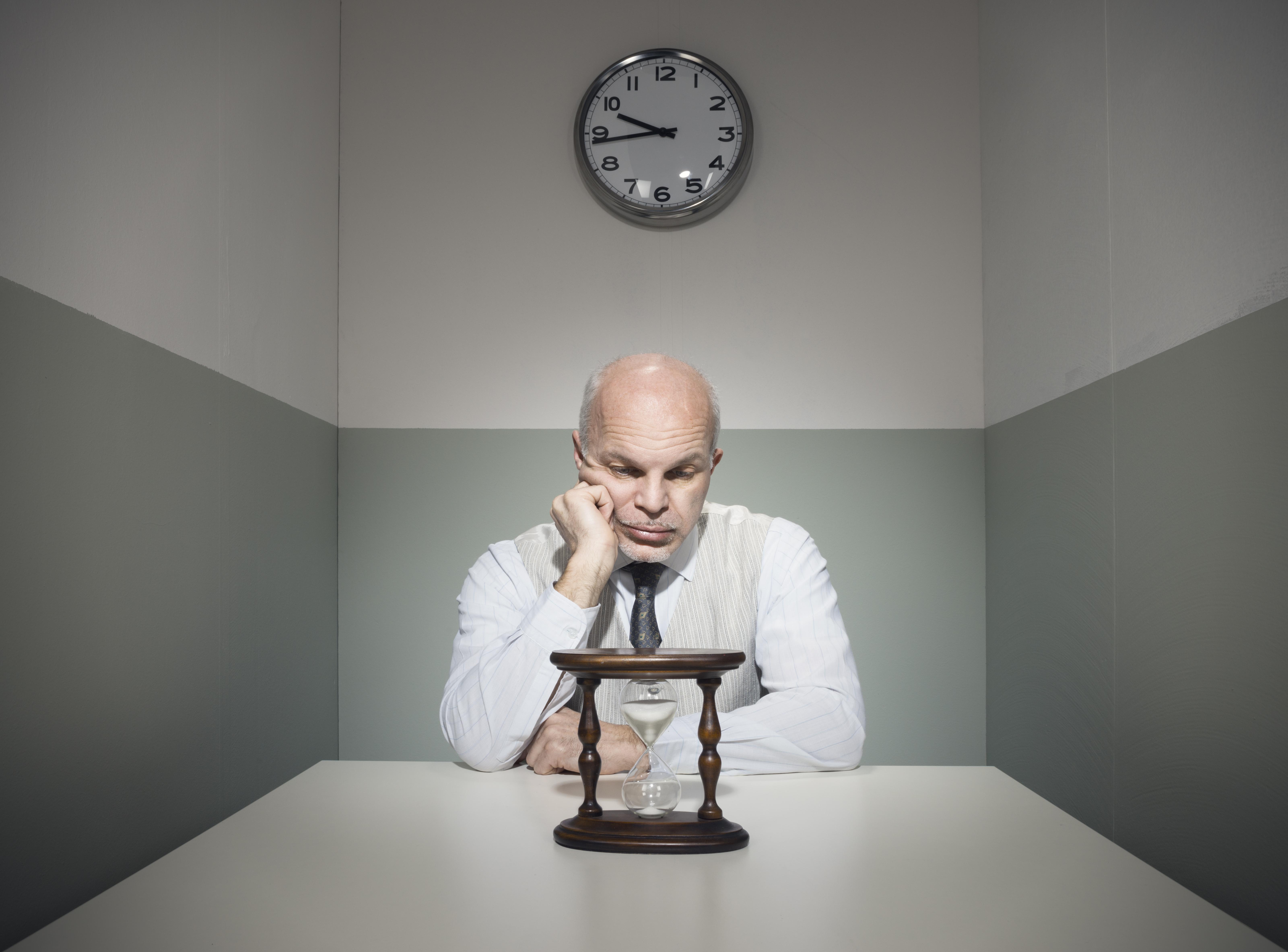 Man staring at hourglass