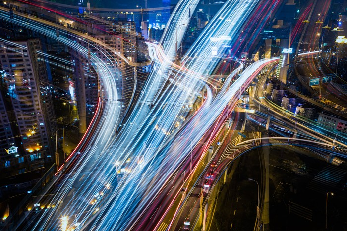Aerial image of city streets lit up by car lights at night.