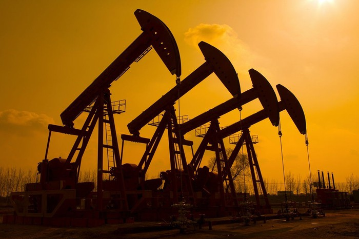 Pumpjacks in an oil field, silhouetted against the sun.