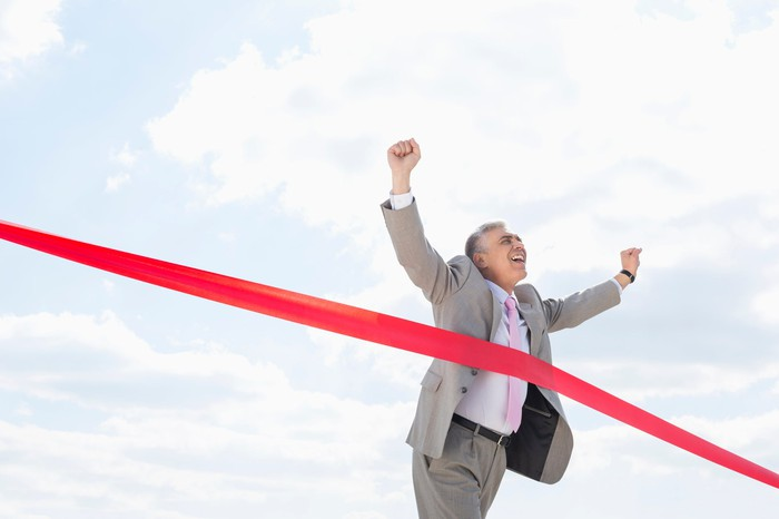 Man in suit running through red tape at finish line