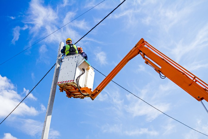 An aerial lift being used to lift a worker installing distribution lines.