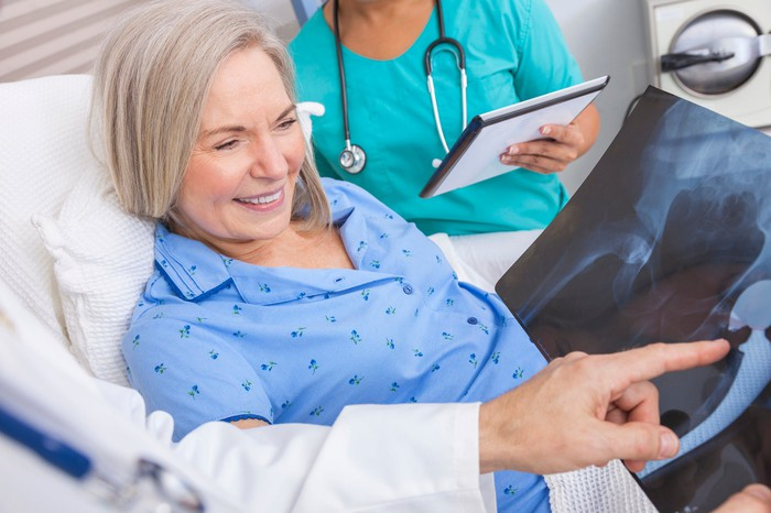 Physician and nurse explaining surgery X-ray to older female patient.