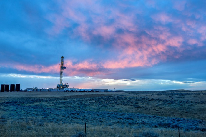 Drilling rig against a blue- colored sunset.