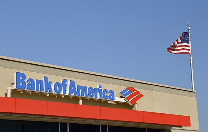 An American flag flies above a Bank of America branch.