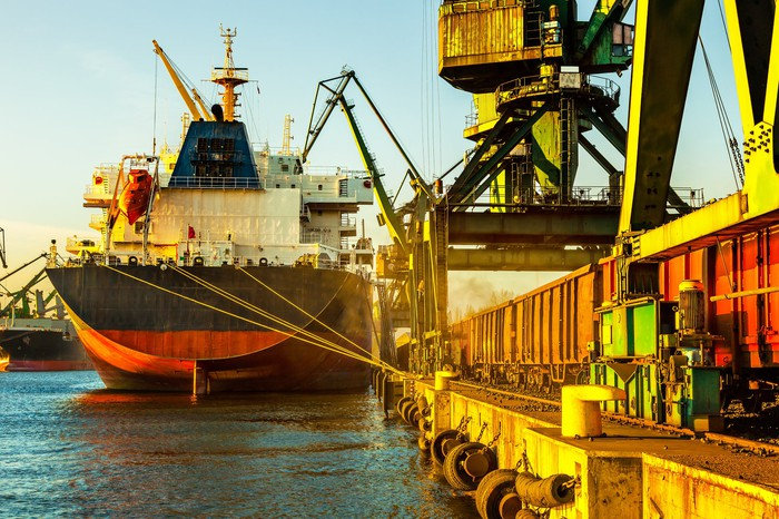 Industrial cargo ship with working crane in port.