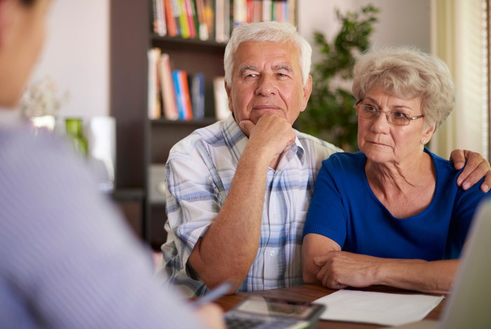 Senior couple talking to a financial planner looking serious