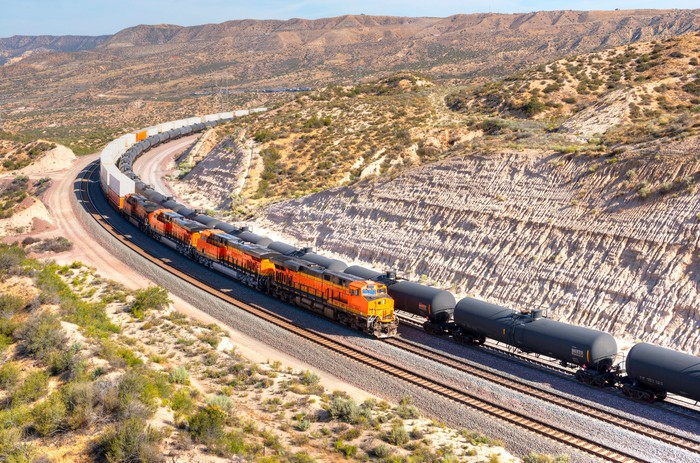 A long train loaded with double-stack white cargo containers winds its way around tight s-curves in mountain countryside.