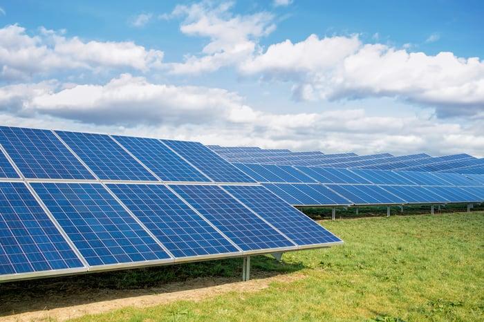 A utility solar farm in a grassy area on a sunny day.