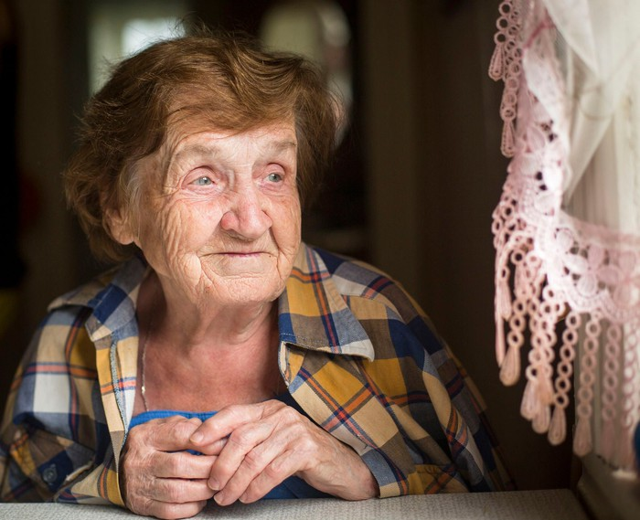 Smiling elderly woman sitting at her table and looking out the window