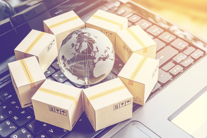 Miniature packages surrounding a globe, all sitting on a laptop keyboard