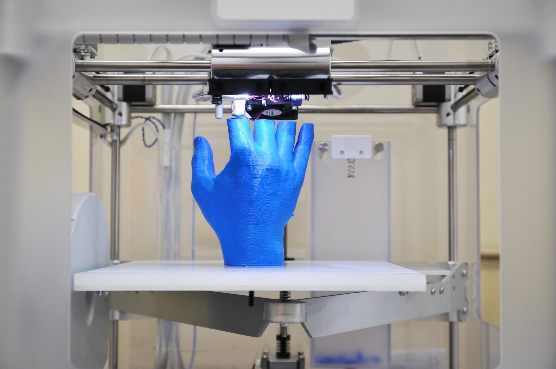 3D printer printing a blue hand.