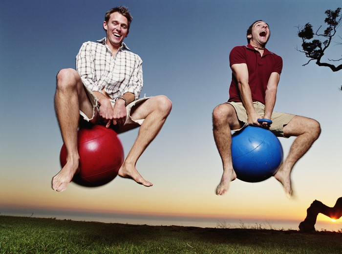 Two men in their 20s bounce down a hill on Hoppity Hops.