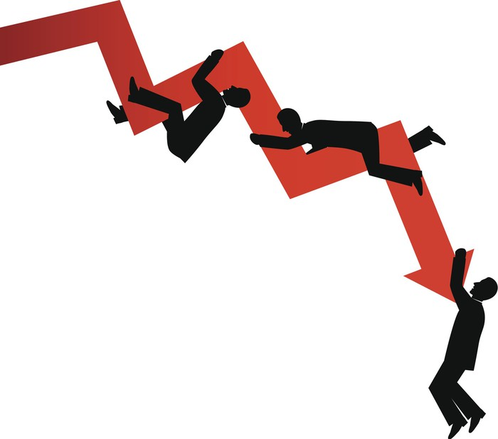 Businessmen silhouettes hanging off a downward sloping graph.