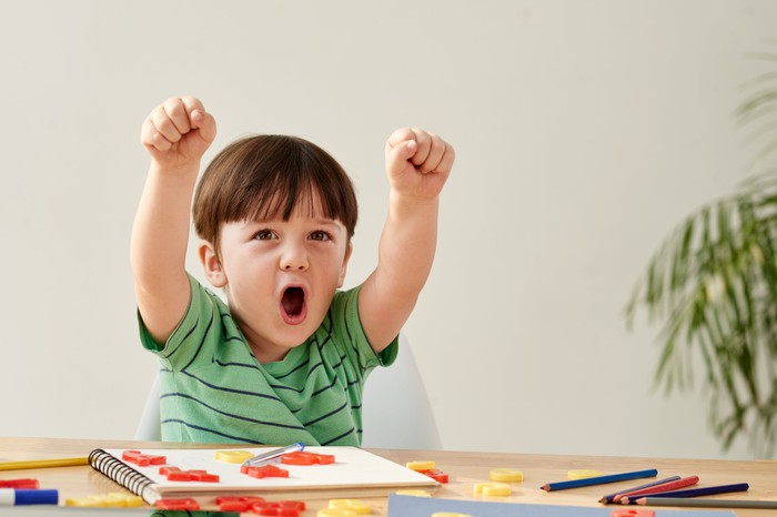 Picture of boy playing at a table with his hands in the air.