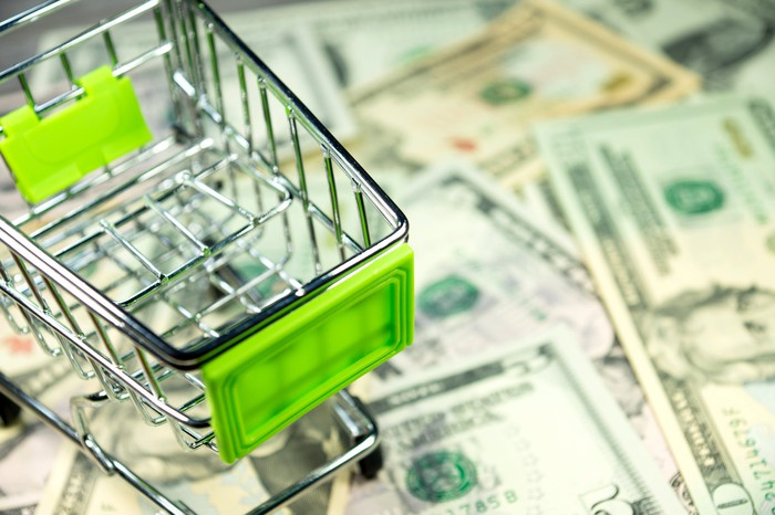 Little shopping cart being pushed over dollar bills.
