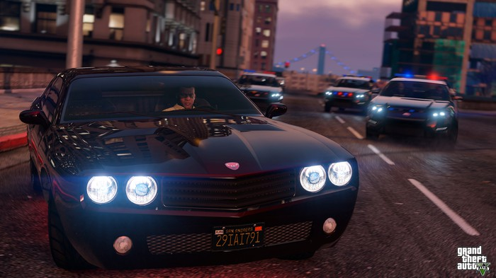 "Screenshot of ""Grand Theft Auto V"" featuring a man in a car being chased by three police cars."