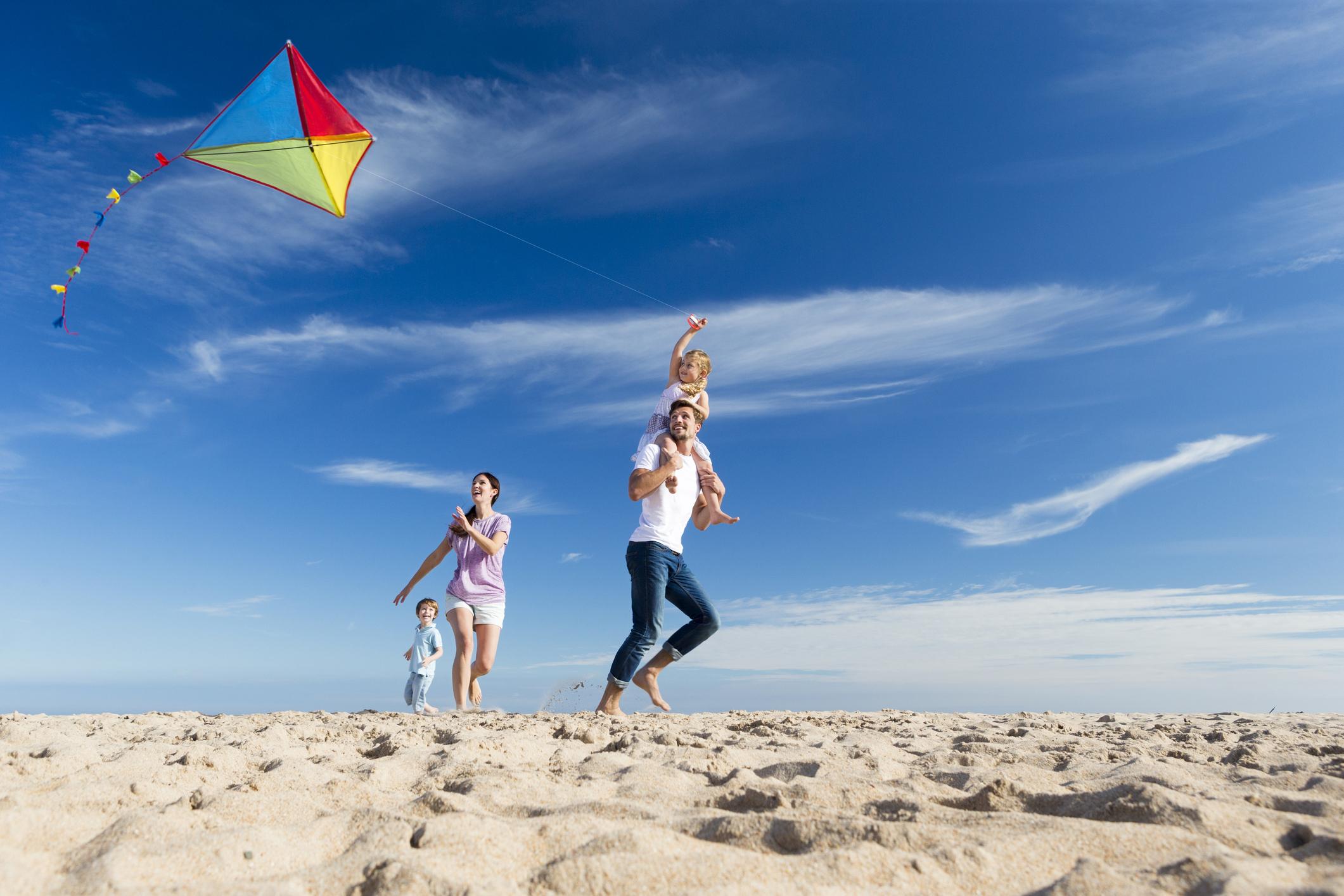 A family flies a kite on a beach.