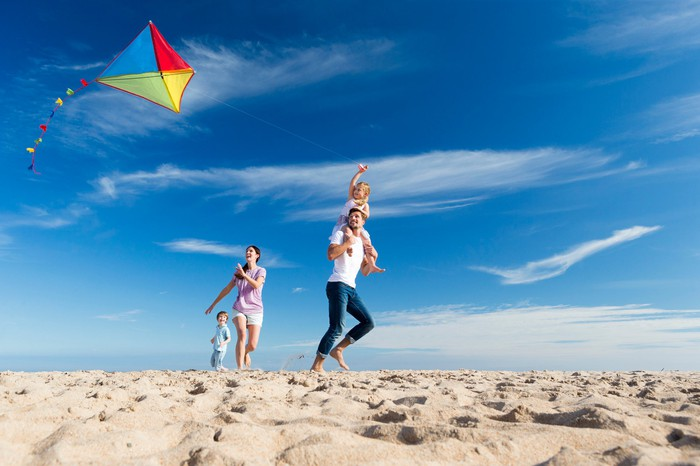 A family flies a kite on a beach.