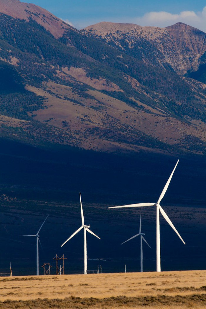Several wind turbines in front of mountains.