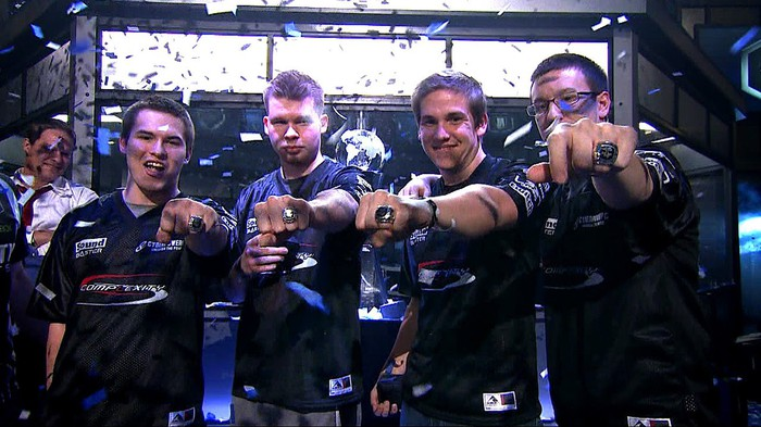 A group of four gamers showing off championship rings from e-sports events.