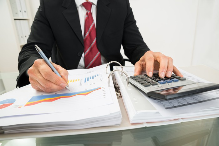 Accountant reviewing paperwork with a calculator.