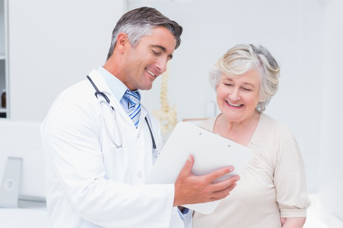Doctor reviewing paperwork with an elderly female patient.