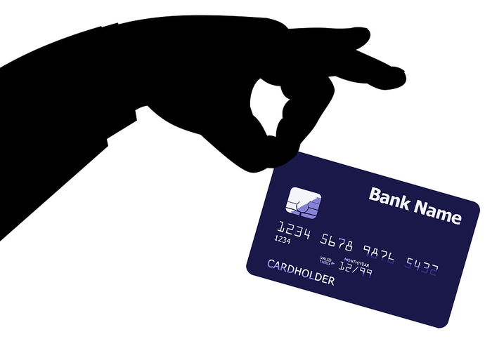 Silhouette of a hand pick-pocketing a credit card