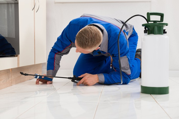 Exterminator treating a house with chemicals.