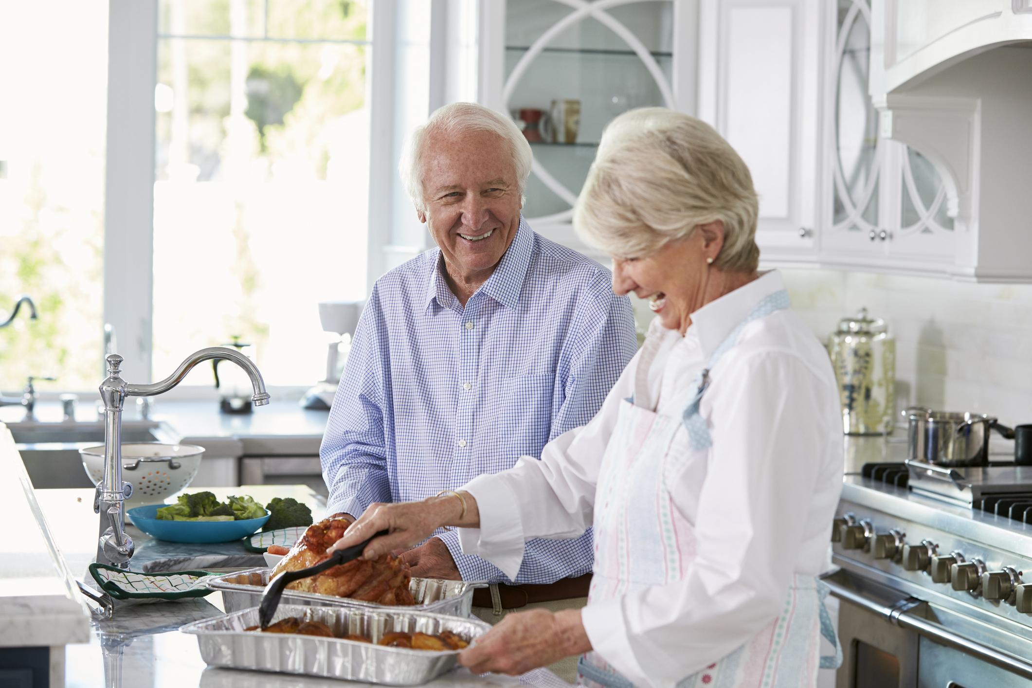 Senior couple cooking a turkey