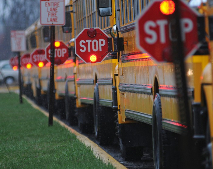 A line of school buses parked along a road with their stop signs out