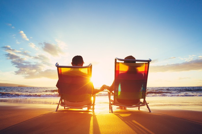 A couple sits on beach chairs holding hands and watching the sun set.