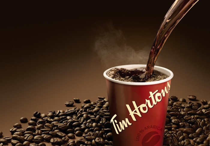 A cup of Tim Horton's coffee being poured surrounded by coffee beans.
