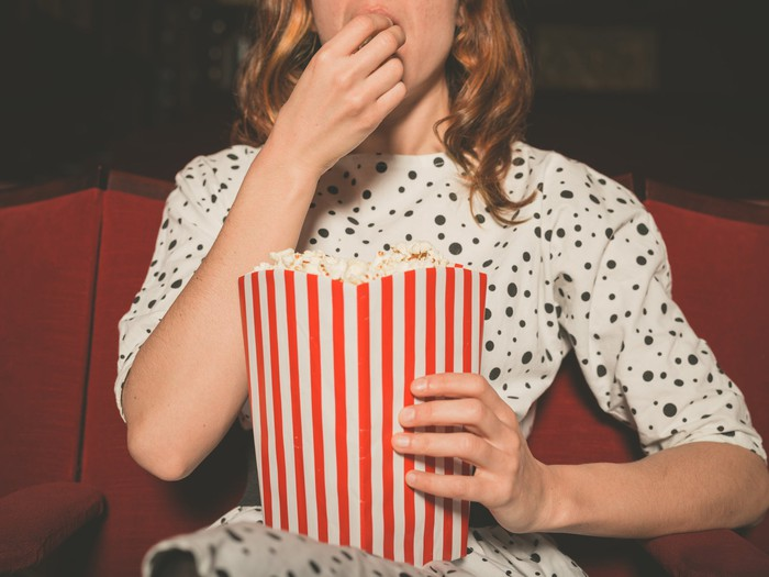 Picture of a woman sitting in a movie theater eating popcorn.