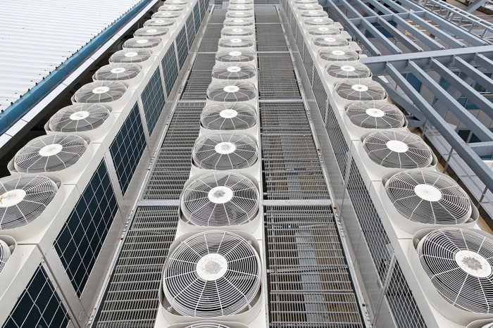 Rows of multiple air conditioning units on top of a building