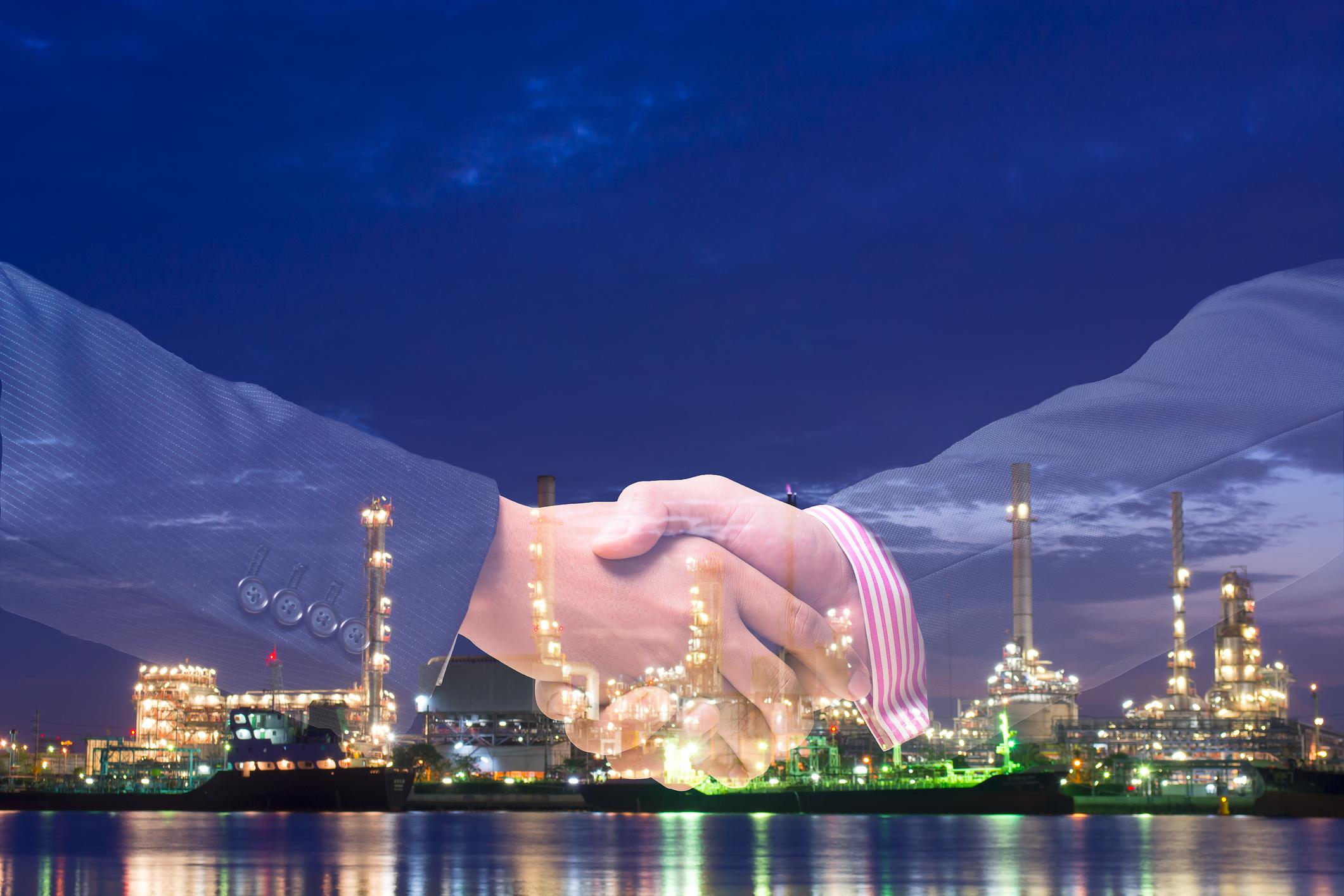 Double exposure of handshake and energy plant.