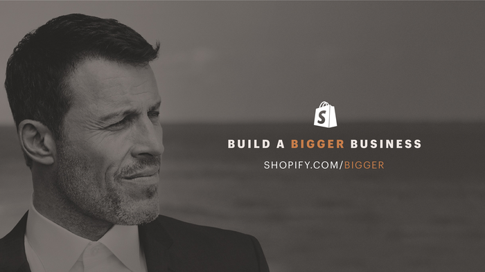 Tony Robbins looking at a logo for Shopify's Build a Bigger Business competition.