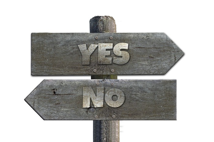 a signpost with one sign saying yes and one saying no, pointing in opposite directions