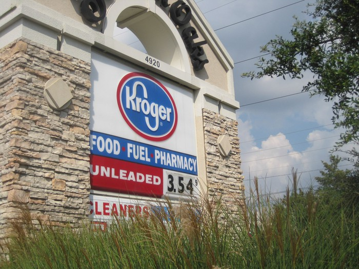 A Kroger sign behind grass showing gas prices