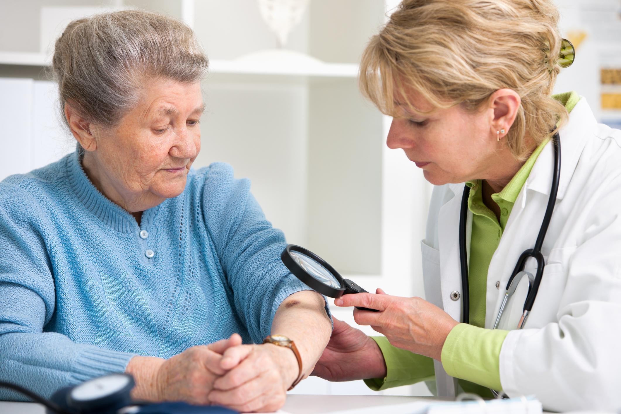 Dermatologist examining skin of an elderly patient.