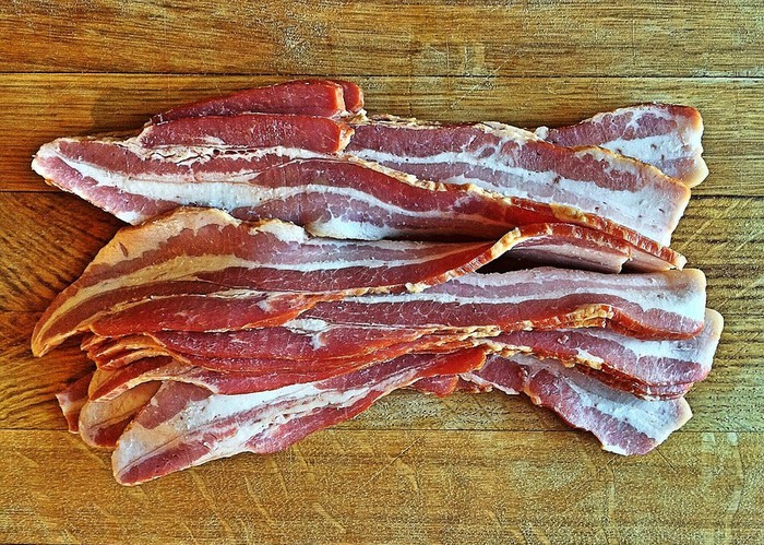Slices of uncooked bacon.