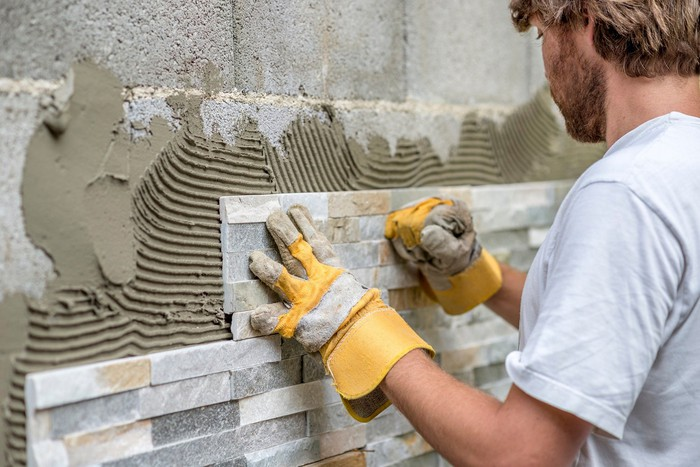 Professional contractor installing wall tile.