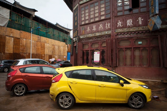 A yellow Ford Fiesta parked near a building in China