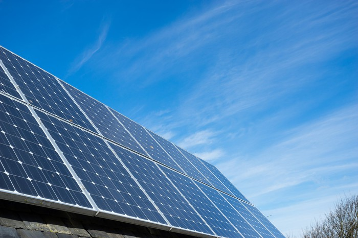 Image of solar panels on a roof in the daytime.