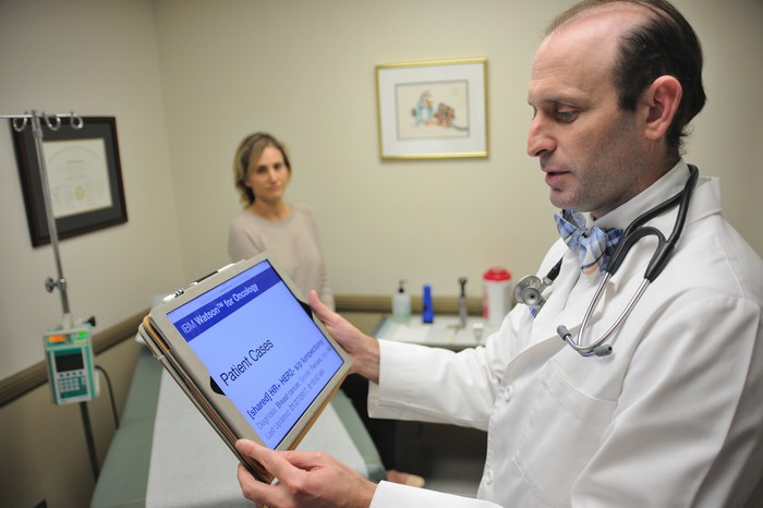 Doctor conferring with Watson AI interface on a tablet computer.